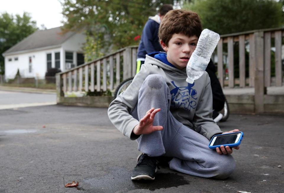 "Shane Bradley, 12, showed off his ""bottle flipping'"" skills while visiting the home of James Tobin in West Roxbury."